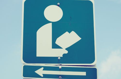 A sign using a symbol to give directions to a public library