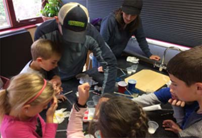 Parents and students perform experiments at Super Science Saturday.