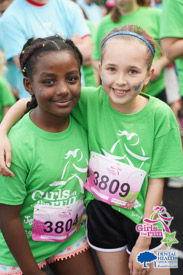 Two girls at a race with bib numbers and Girls on the Run t-shirts.