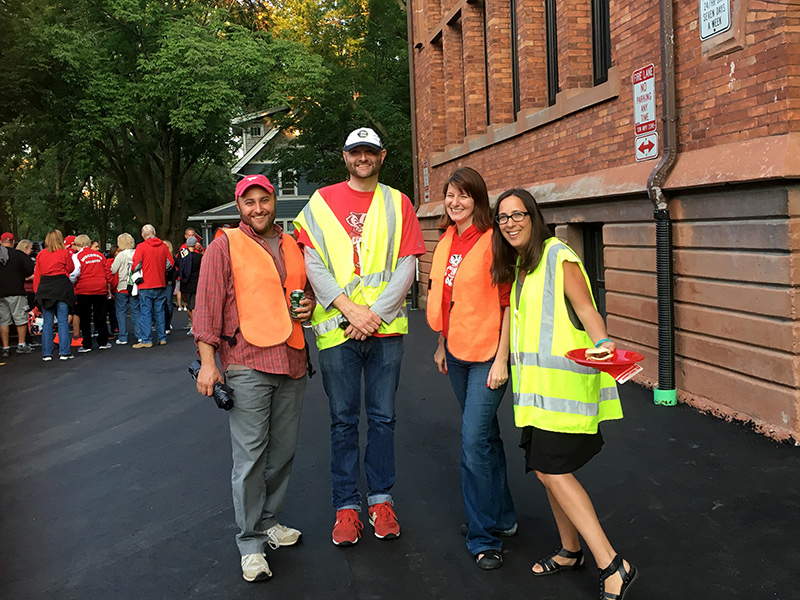Volunteers help direct traffic and park cars during a Badger game.