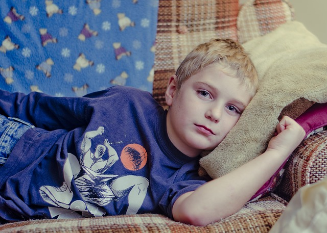 An ill boy lies on a couch. Image by RachelBostwick from Pixabay.