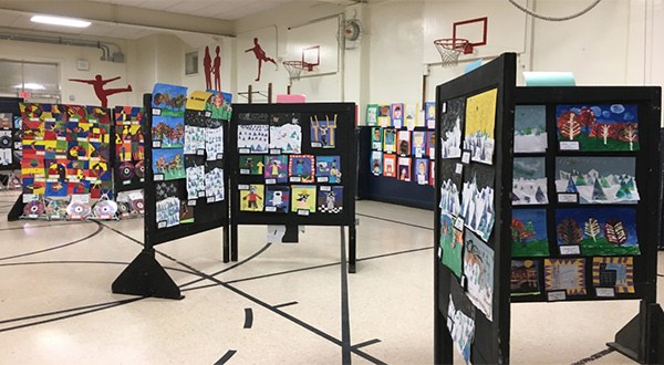 Several stands of artwork are displayed at Gallery Night at Randall School.