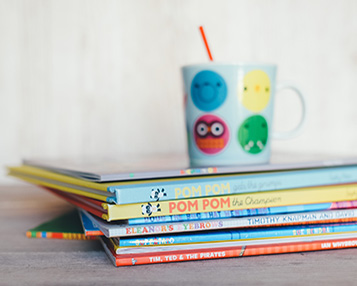 A stack of kids' books with a child's cup on top.