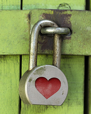 A door locked with a padlock, which has a heart engraved on it.