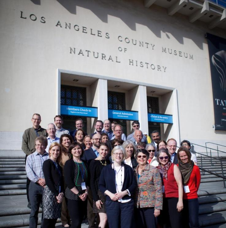 Group of people standing on stairs in front of a building labeled Los Angeles County Museum of Natural History