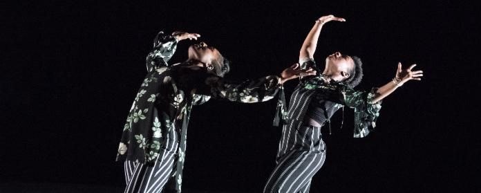 Two women, wearing gorgeous floral tops and stripped pants, dance in a dark space.