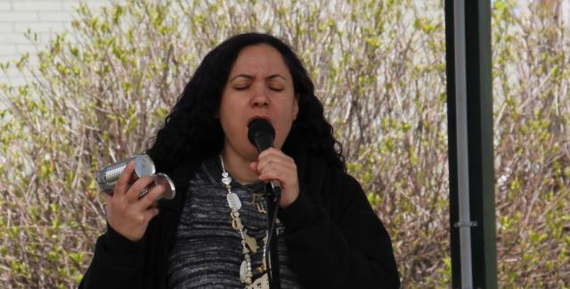 A woman in a chunky necklace sings into a microphone.