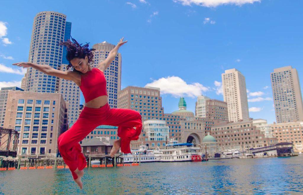 A woman in a red costume leaps with arms outstretched with a sunny blue sky and the waterfront of Boston in the background
