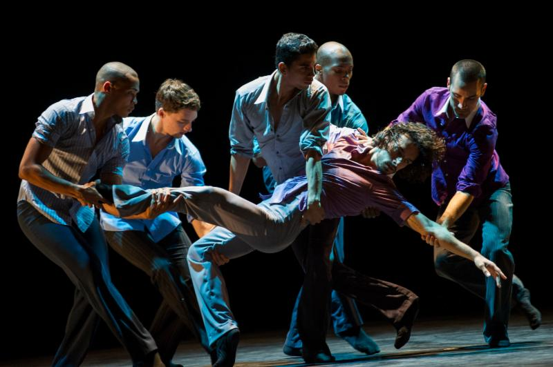 Five male dancers carry a man, leaning away from them, across the stage.