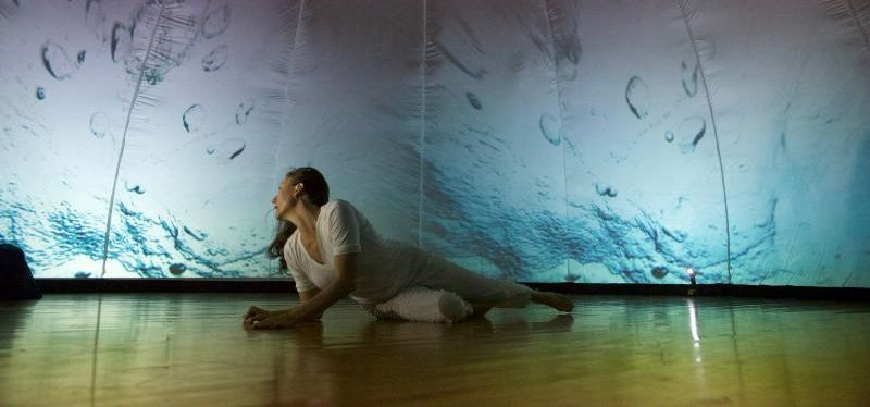 A woman lays in front of a projection of water.
