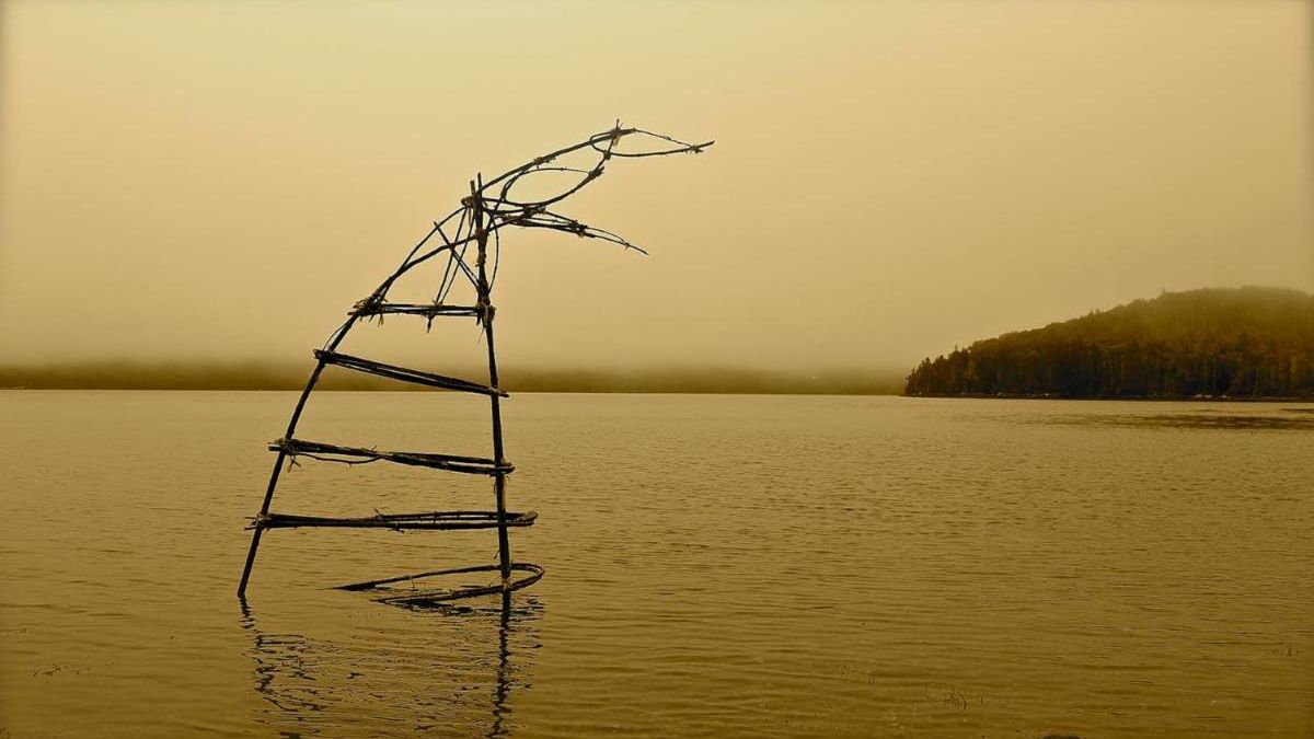 Saplings woven into a whale tail breaching from the tide line of the harbour.