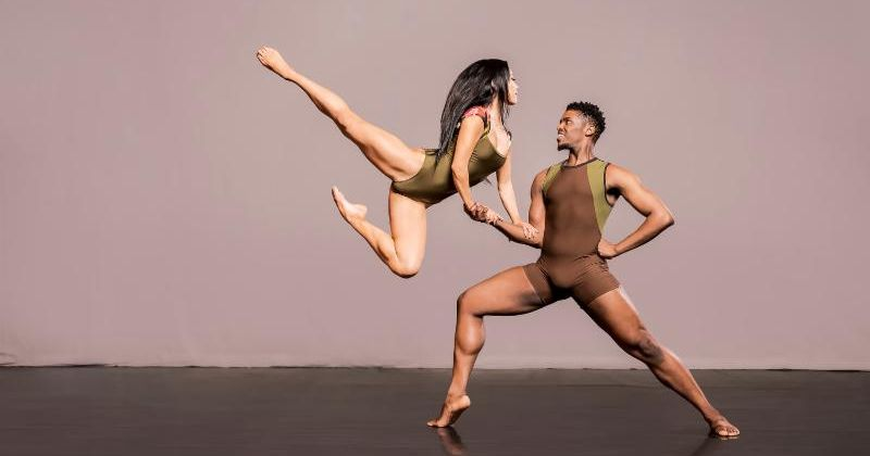 Two dancers, in front of a cream backdrop and wearing leotards, perform. One leaps while leaning on the arm of the other.