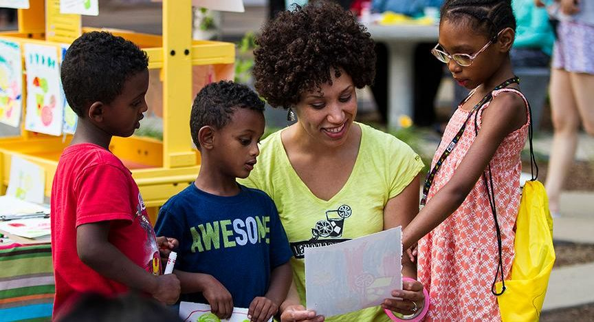 A woman looks at a sheet of paper with three children.
