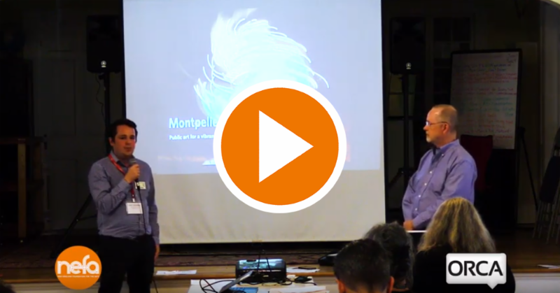 "Two men speak in front of a crowd. An orange ""play"" button is superimposed on top."