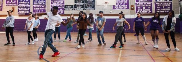 In a high school gymnasium, a man in a white tee leads a group of teenagers in a dance.