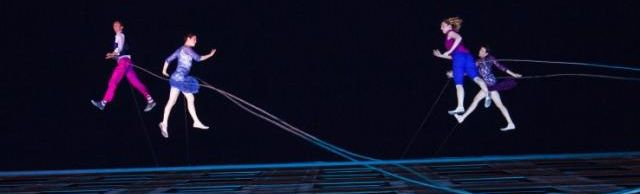 Dancers perform on wires on the side of a tall building at night.