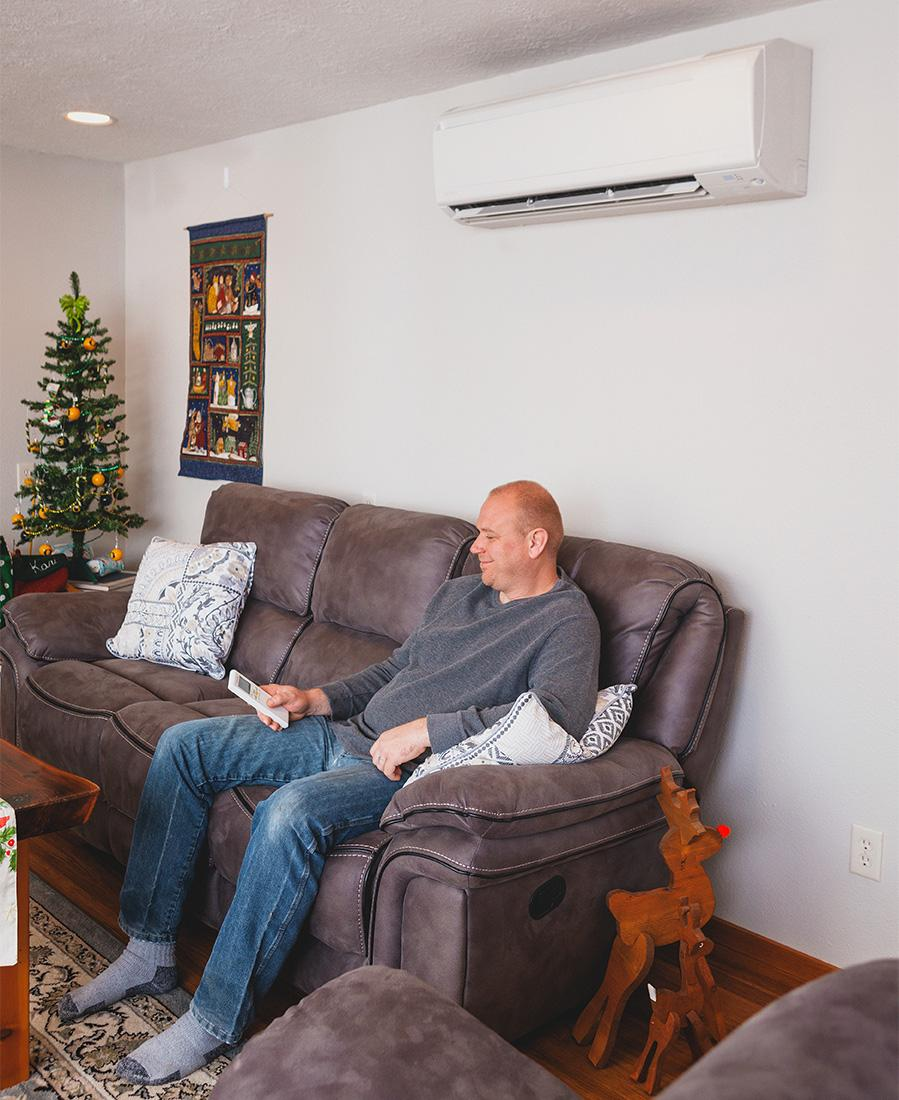 A man controls his ductless heat pump from the comfort of his couch.