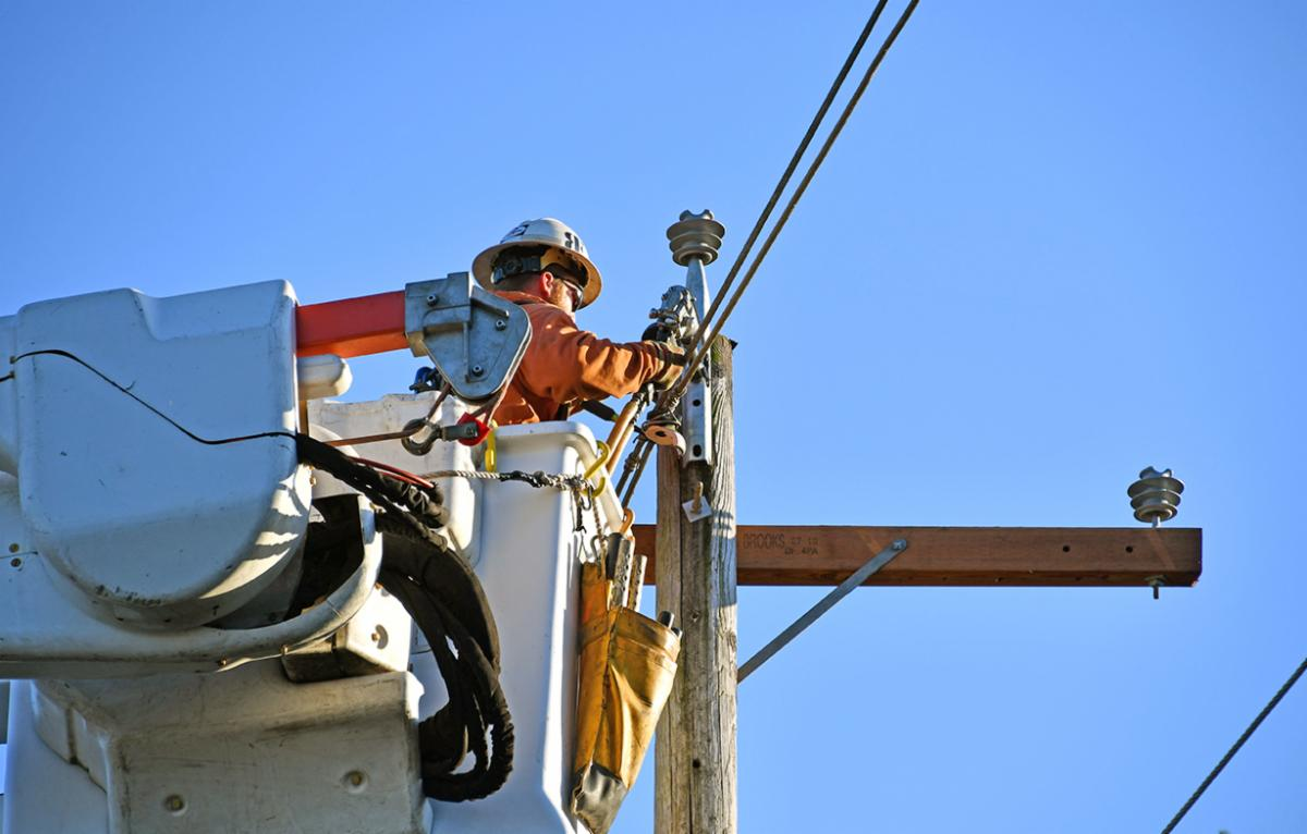 A lineman works to repair a power pole.