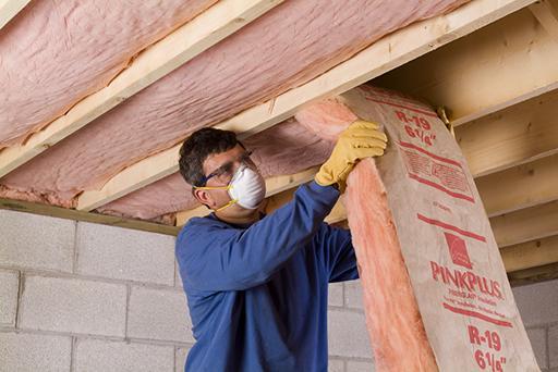 A man installs insulation.